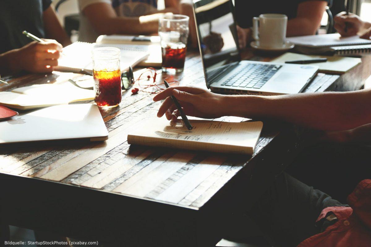 Man sieht einen Tisch, an dem mehrere Personen mit Laptop, Notizbüchern, Stiften und Getränken sitzen