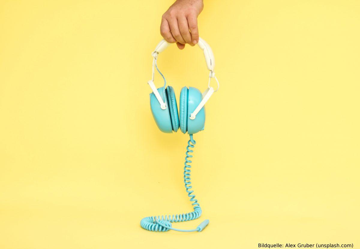 Eine Hand hält türkisfarbene Kopfhörer vor einem gelben Hintergrund